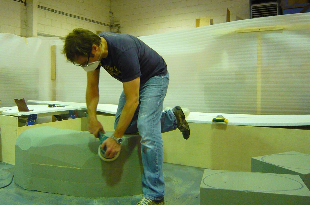 Adam sculpting boulders at Parkway Interiors with an electric grinder.